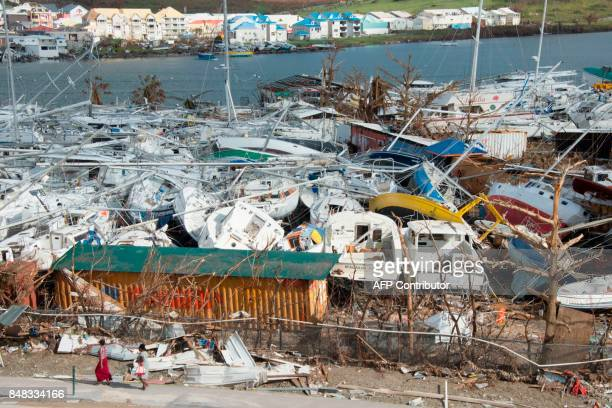 TOPSHOT People walk past smashed boats on September 16 2017 at Marigot shipyard on the French Caribbean island of Saint Martin after the island was...