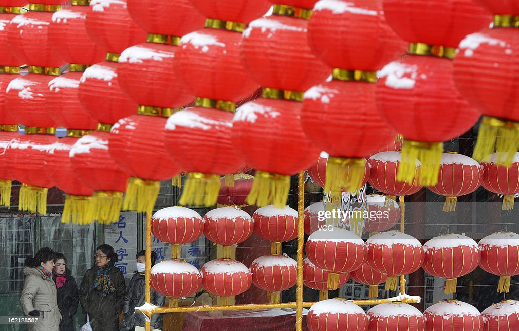 People walk past snow-covered red lanterns on February 18, 2013 in Lanzhou, China. Heavy snow hit large areas of east China on Tuesday.