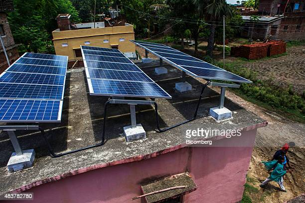 People walk past solar panels mounted on the roof of a building part of a solar power microgrid in the village of Dharnai in Jehanabad Bihar India on...
