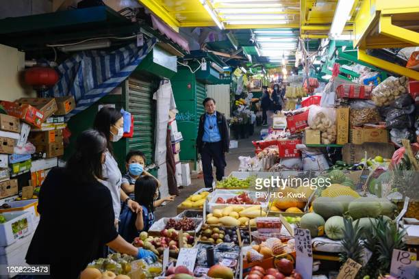 People walk past some fruit stall during a coronavirus outbreak on March 26 2020 in Hong Kong China Latest statistics showed Hong Kong tourist...