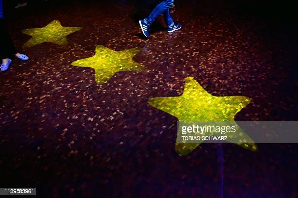 People walk past stars of the European Union flag at the launch of the conservatives CDU/CSU European election campaign in Muenster western Germany...
