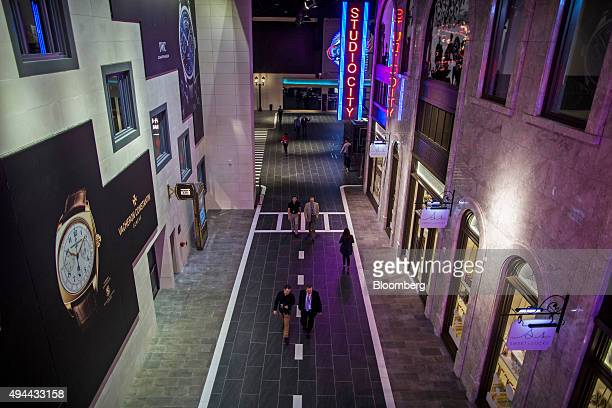 People walk past stores on The Boulevard at Studio City casino resort developed by Melco Crown Entertainment Ltd in Macau China on Tuesday Oct 27...