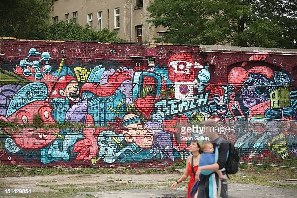 People walk past street art in Dirschauer Strasse in Friedrichshain district on June 26 2014 in Berlin Germany Berlin with its long tradition of...