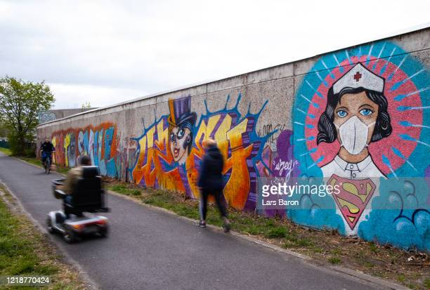 People walk past street art painted by artist Kai 'Uzey' Wohlgemuth featuring a nurse as Superwoman on April 14, 2020 in Hamm, Germany. So far, over...