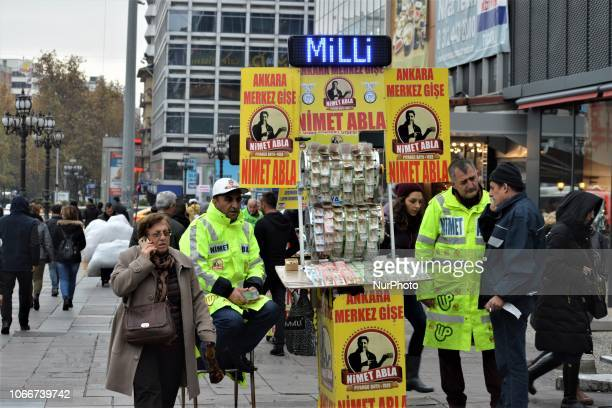People walk past street vendors selling New Year's lottery tickets in the Kizilay district of Ankara Turkey on November 30 2018 This year's lottery...