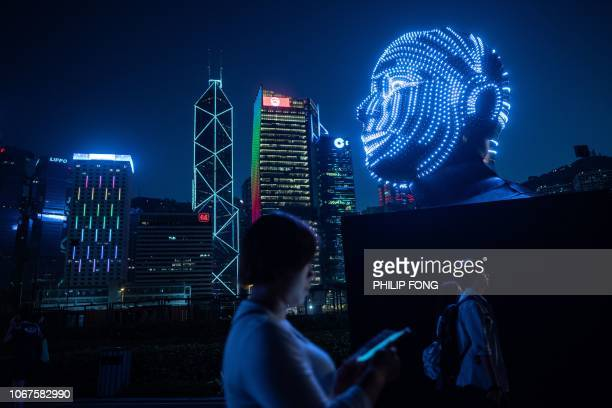 TOPSHOT People walk past 'Talking Heads' by Viktor Vicsek of Hungary during the Hong Kong Pulse Light Festival on December 2 2018 / RESTRICTED TO...