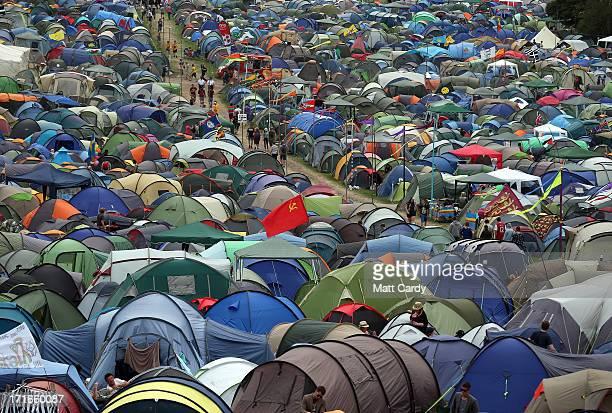 People walk past tents at the Glastonbury Festival of Contemporary Performing Arts site at Worthy Farm Pilton on June 27 2013 near Glastonbury...