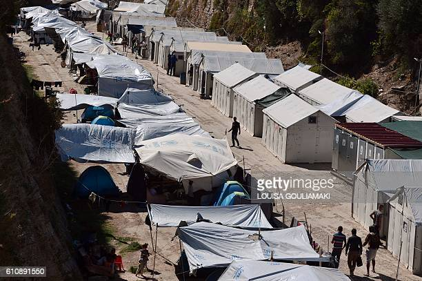 People walk past tents at the municipalityrun Souda migrant camp in the city of Chios on September 28 2016 The EU said on September 28 it hopes to...