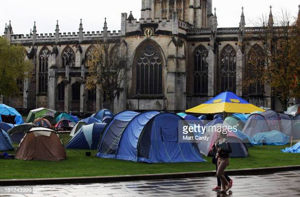 People walk past tents belonging to anticapitalist protestors at the Occupy Bristol protest camp on November 3 2011 in Bristol England The...