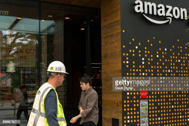 People walk past the Amazon Go grocery store at the Amazon corporate headquarters on June 16 2017 in Seattle Washington Amazon announced that it will...