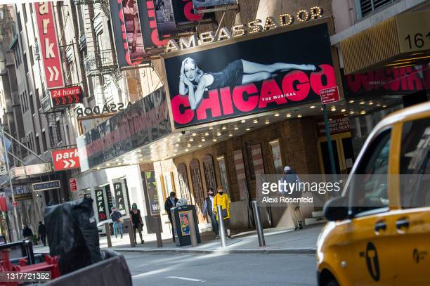 """People walk past the Ambassador Theatre, home to """"Chicago the Musical,"""" in Times Square on May 12, 2021 in New York City. """"Hamilton"""", """"The Lion..."""