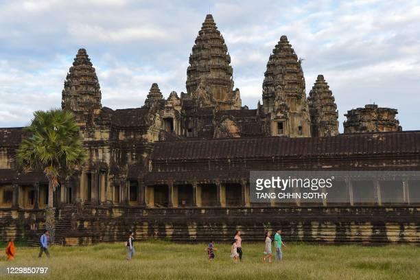 People walk past the Angkor Wat temple in Siem Reap province on November 29, 2020.