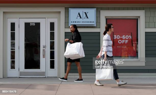 People walk past the Armani Exchange store at the Woodbury Common Premium Outlets Mall on October 21 2017 in Central Valley NY