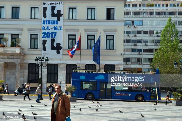 People walk past the Athens city hall drapped with a banner advertising the 14 Documenta contemporary arts exhibition on April 6 2017 Documenta is an...