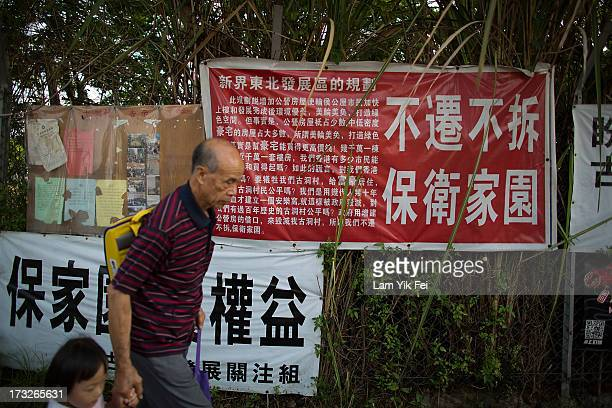 People walk past the banner reading ''Protect Our Home'' in Ma Tso Lung Village on July 11 2013 in Hong Kong China The North East New Territories New...