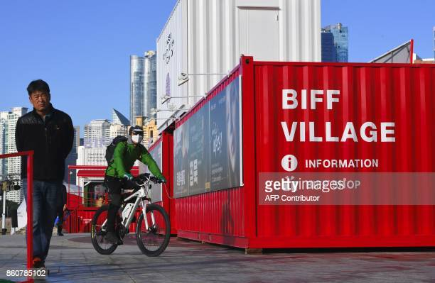 People walk past the BIFF Village a venue of the 22nd Busan International Film Festival at Haeundae beach in Busan on October 13 2017 BIFF will...