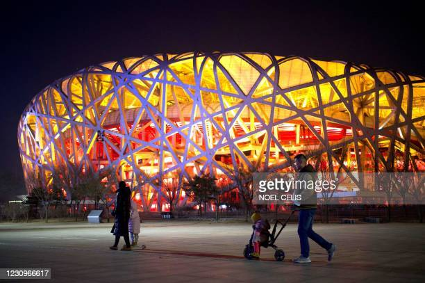 People walk past the Birds Nest stadium, the venue for opening and closing ceremonies at the 2022 Winter Olympics, in Beijing on February 4 a year...