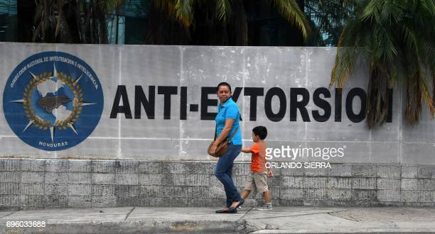 People walk past the building of the National AntiExtortion Police in Tegucigalpa on June 14 2017 Public transport workers and passengers in this...