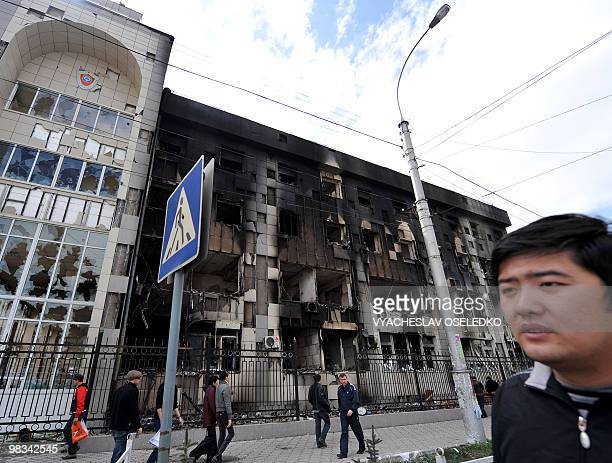 People walk past the burnt offices of the General prosecutor in Bishkek on April 8 2010 UN chief Ban Kimoon said today he will send a special envoy...