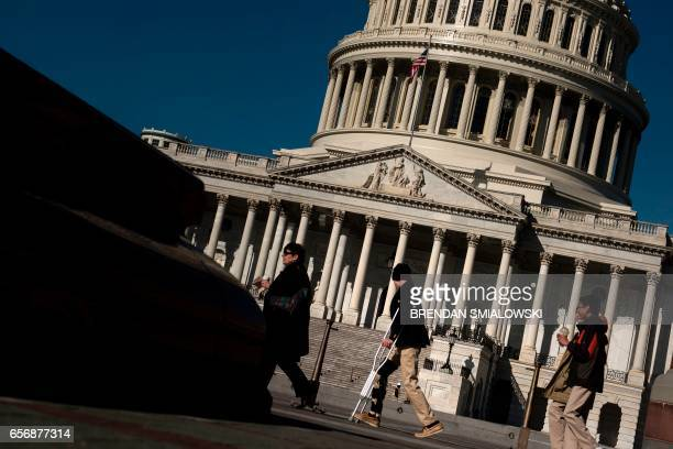 People walk past the Capitol Dome on Capitol Hill on March 23 2017 in WashingtonDC / AFP PHOTO / Brendan Smialowski