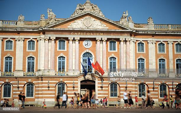 People walk past the Capitole which houses the city hall of the French southwestern town of Toulouse on July 9 2011 AFP PHOTO / REMY GABALDA