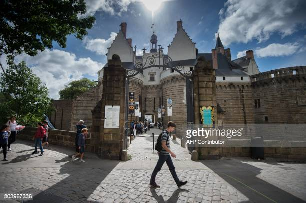 People walk past the Castle of Nantes on June 29 2017 during the 6th edition of the 'A journey to Nantes' art festival which runs until August 27...