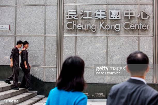 People walk past the Cheung Kong Center headquarters of CK Hutchinson Holdings in Hong Kong on March 21 2019