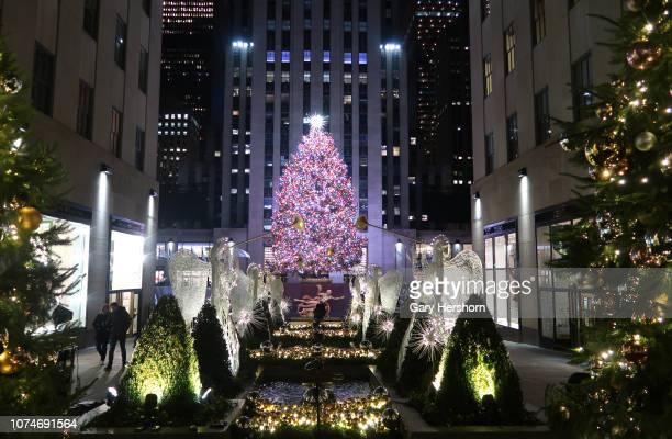 People walk past the Christmas tree in Rockefeller Center before sunrise on November 29, 2018 in New York City.