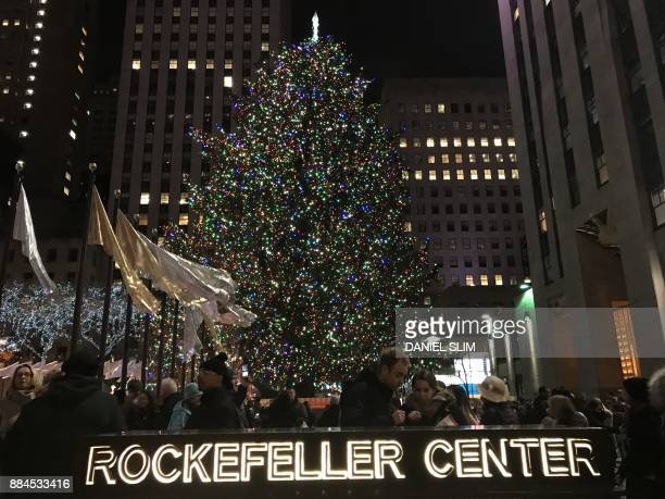 People walk past the Christmas Tree in Rockefeller Center in New York on December 1 2017 / AFP PHOTO / Daniel SLIM