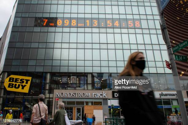 """People walk past the """"Climate Clock"""" in Union Square as the city continues Phase 4 of reopening following restrictions imposed to slow the spread of..."""