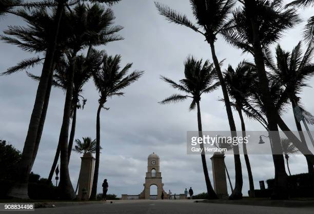 People walk past the clock tower at the entrance to Worth Avenue on January 21 2018 in Palm Beach Florida