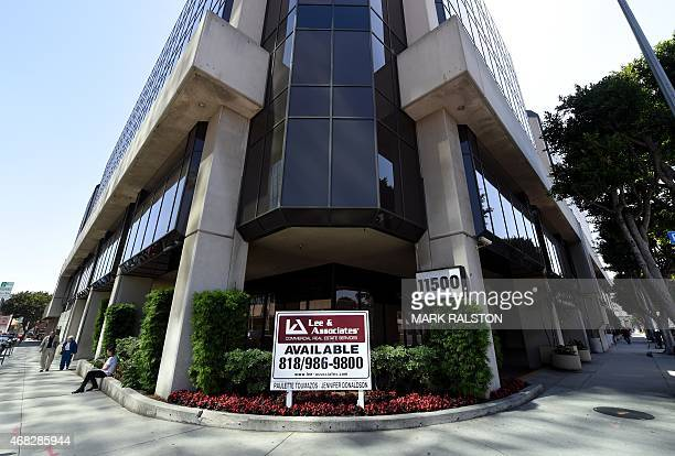 People walk past the commercial building containing the headquarters of Bikram Yoga in Los Angeles California on April 1 2015 Yoga guru Bikram...