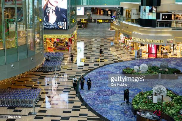 People walk past the departure hall after check in counter at Changi Airport Terminal 3 on November 11, 2020 in Singapore. Singapore and Hong Kong...