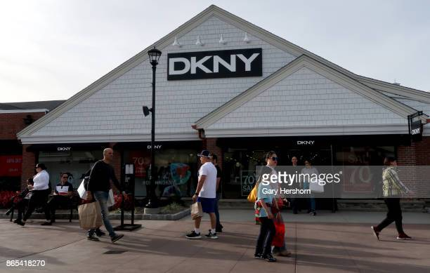 People walk past the DKNY store at the Woodbury Common Premium Outlets Mall on October 21 2017 in Central Valley NY
