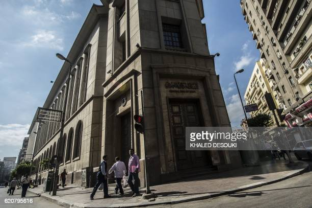 People walk past the Egyptian Central Bank in downtown Cairo on November 3 2016 Egypt floated the country's pound as part of a raft of reforms after...
