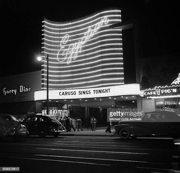 People walk past the Egyptian Theatre on Hollywood Boulevard at night in HollywoodCalifornia