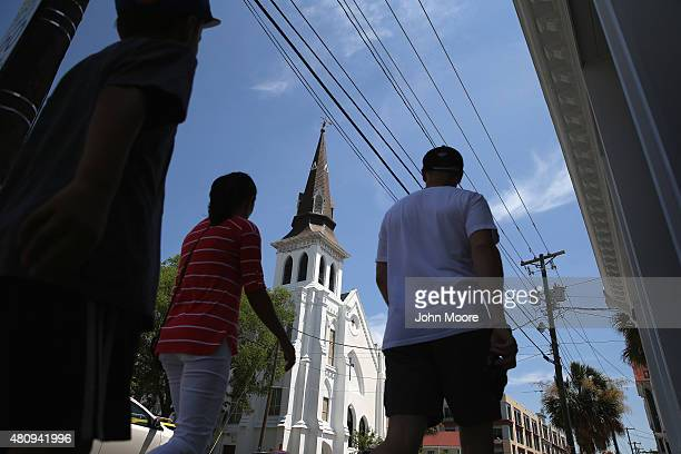 People walk past the Emanuel African Methodist Episcopal church on July 15 2015 in downtown Charleston South Carolina A makeshift shrine of flowers...
