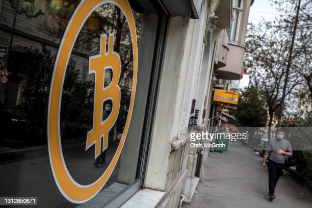 People walk past the entrance of a cryptocurrency exchange office on April 16, 2021 in Istanbul, Turkey. Turkey's Central Bank announced a ban on the...