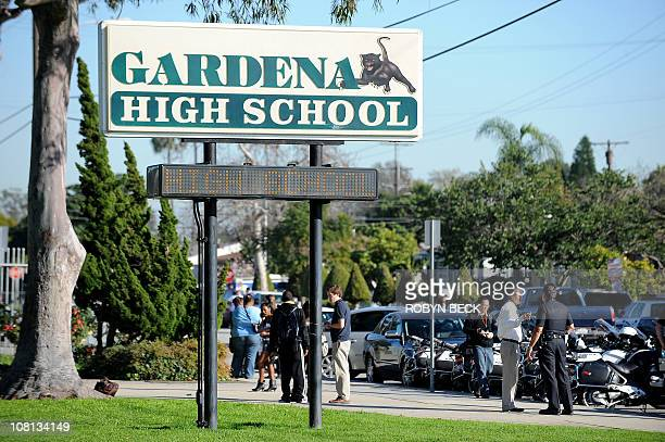 People walk past the entrance to Gardena High School in Gardena, California January 18, 2011 after two students were shot, one in the head, when a...