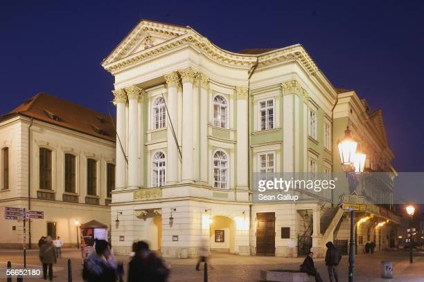 People walk past the Estates Theatre where in 1787 Austrian composer Wolfgang Amadeus Mozart premiered his 'Don Giovanni' opera January 23 2006 in...
