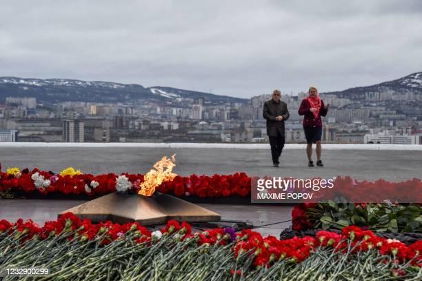 People walk past the eternal flame memorial dedicated to WWII in Murmansk on May 14, 2021.