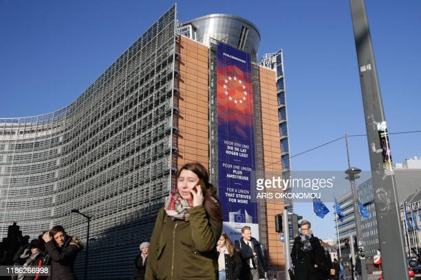 People walk past the European Commission headquarters with a new banner with the lettering reading 'For a union that strives for more' in different...