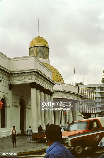 People walk past the facade and gold dome of the National Assembly building in Caracas, Venezuela, 1970. .