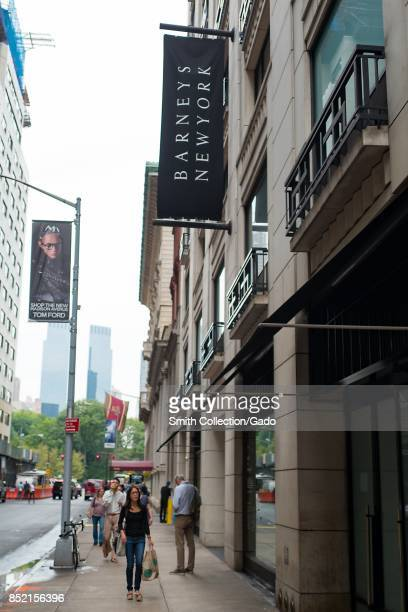 People walk past the facade of the Barneys New York department store on 60th street off Madison Avenue in Manhattan New York City New York September...