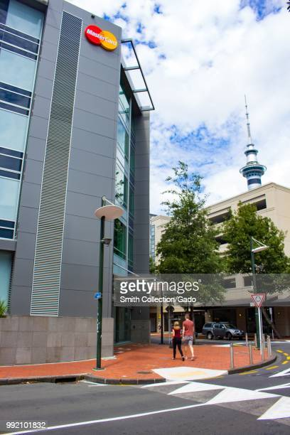 People walk past the facade of the regional headquarters of Mastercard in Auckland, New Zealand, February 26, 2018.