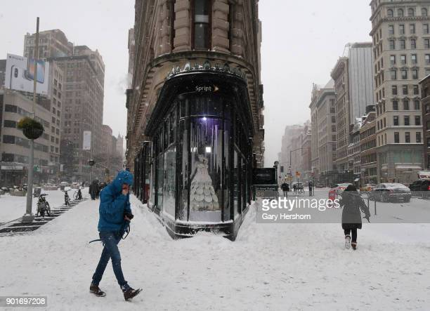 People walk past the Flatiron Building during a winter storm called a 'bomb cyclone' on January 4 2018 in New York City