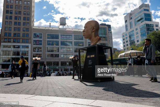 """People walk past the """"FLOYD"""" sculpture duringConfront Art's Exhibition SEEINJUSTICE in Union Square on September 30, 2021 in New York City...."""