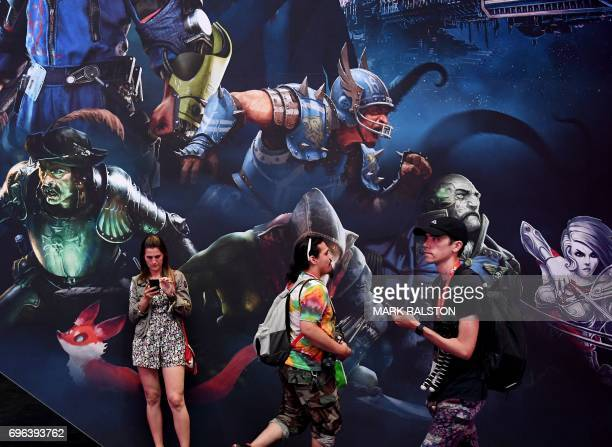 People walk past the Focus Home Interactive display at the Los Angeles Convention center on day three of E3 2017 the three day Electronic...