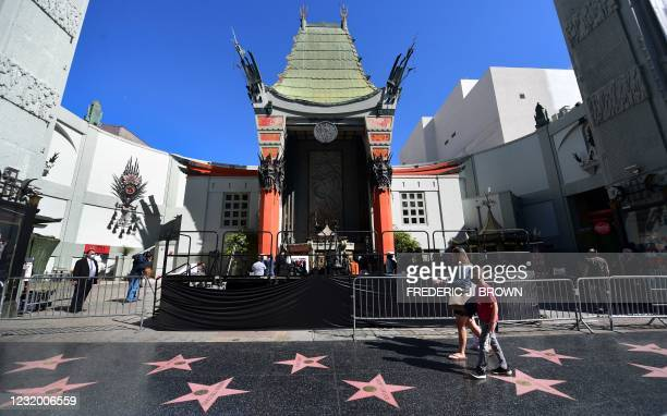 People walk past the forecourt of the TCL Chinese Theater in Hollywood, California on March 29, 2021 where four directors of current and previous...