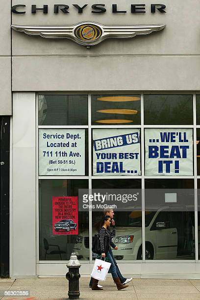 People walk past the front window of the Manhattan Chrysler dealership on April 30 2009 in New York City US carmaker Chrysler today announced it will...